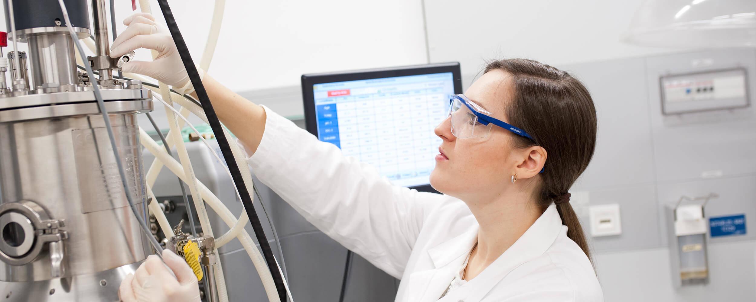 Eine Naturwissenschaftlerin benutzt ein Gerät im Labor